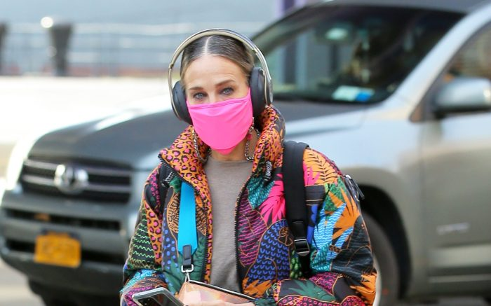 Sarah Jessica Parker Is Seen In A Colorful Coat, Matching Pink Shoes And Face Mask And Backpack Wearing Headphones As She Arrives At Her SJP Collection Shoe Sample Sale In Seaport In New York City