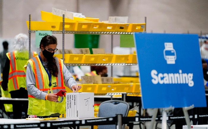 A Philadelphia election worker processes mail-in and absentee ballots for the 2020 general election in the United States at the Pennsylvania Convention Center, Tuesday, Nov. 3, 2020, in Philadelphia. (AP Photo/Matt Slocum)