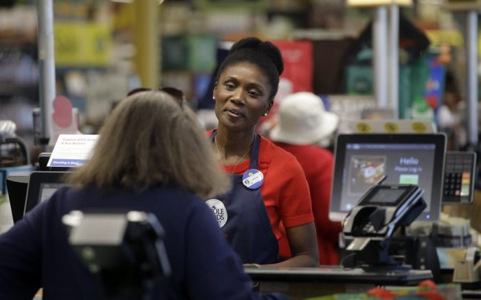 In this May 8, 2018, photo, Nadine Vixama, who emigrated from Haiti eight years ago, works as a cashier at a Whole Foods in Cambridge, Mass. Vixama has taken English classes and a program in store and customer service basics launched by the National Retail Federation trade group though a local organization that helps people gain work skills. (AP Photo/Steven Senne)