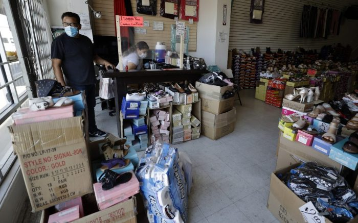 Marco Pinuela, left, looks out the window as he and his wife Irma Pinuela close up their shoe store, Shoes 4 Less, Tuesday, June 30, 2020, in Calexico, Calif. Saddled with a surge in positive cases and hospitalizations for the new coronavirus, a farming region on California's border with Mexico is now forced to backpedal on reopening its battered economy. The Imperial County board of supervisors unveiled a plan late Monday that includes closing businesses deemed non-essential, except for curbside pickup, and shuttering county parks. (AP Photo/Gregory Bull)