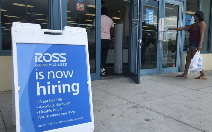 """FILE - In this July 8, 2020, file photo, a """"Now Hiring"""" sign sits outside a Ross Dress for Less store, in North Miami Beach, Fla. The United States added 1.8 million jobs in July, a pullback from the gains of May and June and evidence that the resurgent coronavirus has weakened hiring and the economic rebound. (AP Photo/Wilfredo Lee, File)"""