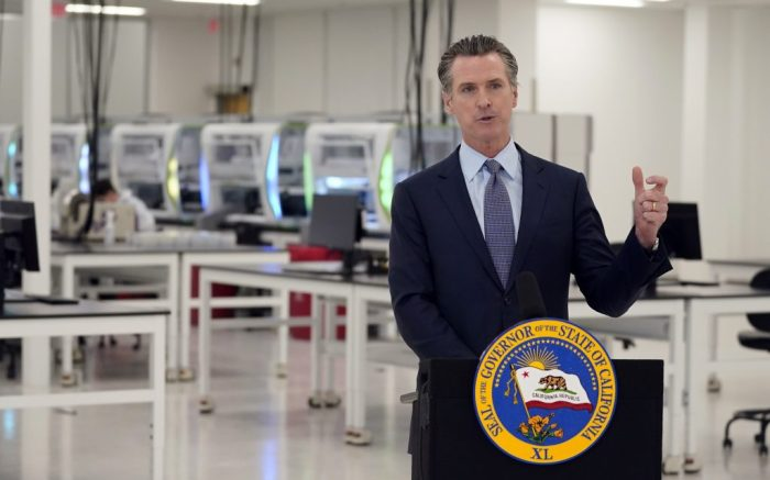 California Gov. Gavin Newsom speaks at a COVID-19 testing facility Friday, Oct. 30, 2020, in Valencia, Calif. Newsom announced the new $120 million, 134,000 sq. foot coronavirus testing facility in Valencia Friday. The state is working with corporate partner PerkinElmer to run the lab which will enable the state to process an additional 150,000 COVID-19 tests per day. (AP Photo/Marcio Jose Sanchez, Pool)