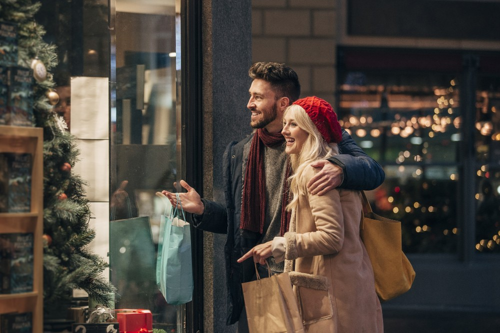 Man and woman shopping for the holidays outdoors store window
