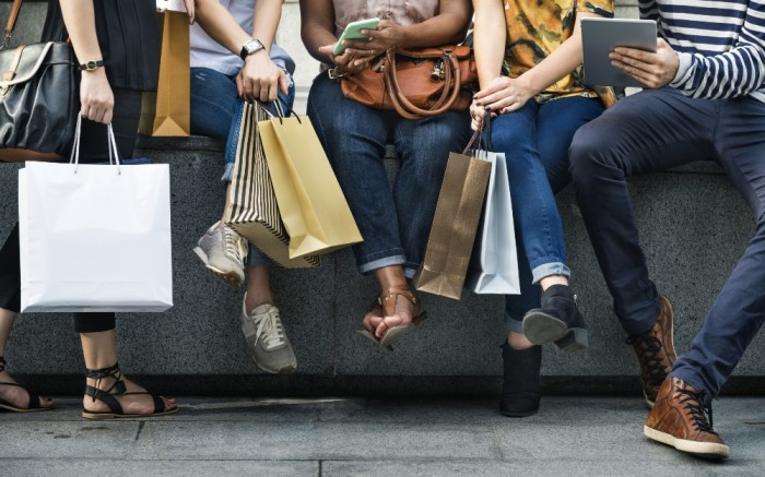 Consumers holding festive shopping bags for holiday purchases