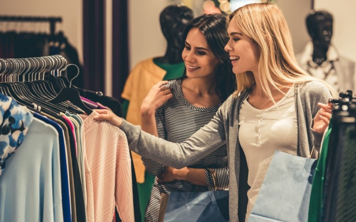 Two women browsing for apparel in-store
