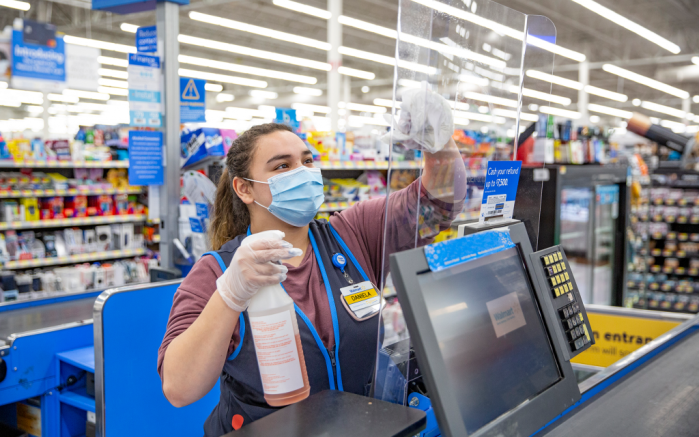 A Walmart associate cleans the plastic shield at a cash register in a store.