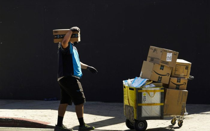 In this Thursday, Oct. 1, 2020, photo an Amazon worker wears a mask and gloves as he delivers boxes downtown Los Angeles. Amazon says that nearly 20,000 of its workers have either tested positive or been presumed positive for COVID-19. Amazon says in a corporate blog Thursday, Oct. 1, that it examined data from March 1 to Sept. 19 for its 1.37 million workers at Amazon and Whole Foods Market. (AP Photo/Damian Dovarganes)