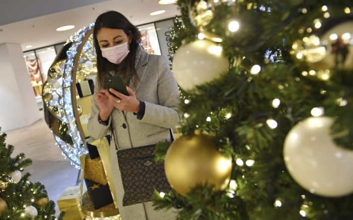 Topic picture prisoners in the coronavirus pandemic on November 26th, 2020. A young woman with face mask and mask is standing with her smartphone, cell phone behind a Weihaftertsbaum and looks at it. Mall, shopping center, pandemic, lockdown, shutdown, incidence value. MODEL RELEASED! | usage worldwide Photo by: Frank Hoermann/SVEN SIMON/picture-alliance/dpa/AP Images