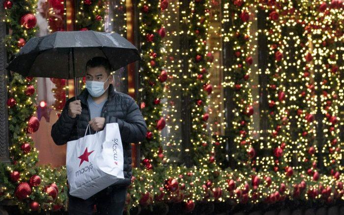 A shopper walks by a holiday window display, Monday, Nov. 30, 2020, in New York. (AP Photo/Mark Lennihan)
