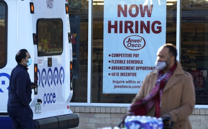 Shoppers enter and exit a grocery store as a hiring sign is seen in Deerfield, Ill., Thursday, Dec. 4, 2020. U.S employers added about 245,000 jobs in November, as companies scaled back their hiring as the viral pandemic accelerates across the country. (AP Photo/Nam Y. Huh)