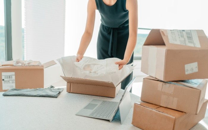 Woman opening or packing a box to return an e-commerce purchase