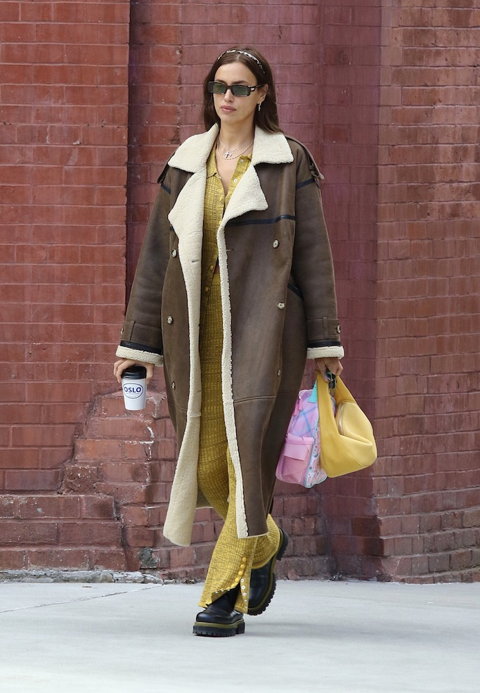 Irina Shayk looks stylish with a yellow outfit and a large brown coat while on a coffee run in Manhattan's West Village area. 22 Jan 2021 Pictured: Irina Shayk. Photo credit: LRNYC / MEGA TheMegaAgency.com +1 888 505 6342 (Mega Agency TagID: MEGA728349_004.jpg) [Photo via Mega Agency]