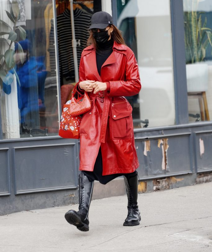 Irina Shayk wears a red leather trench, handbag, and knee-high black combat boots