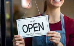Woman holding store sign saying open