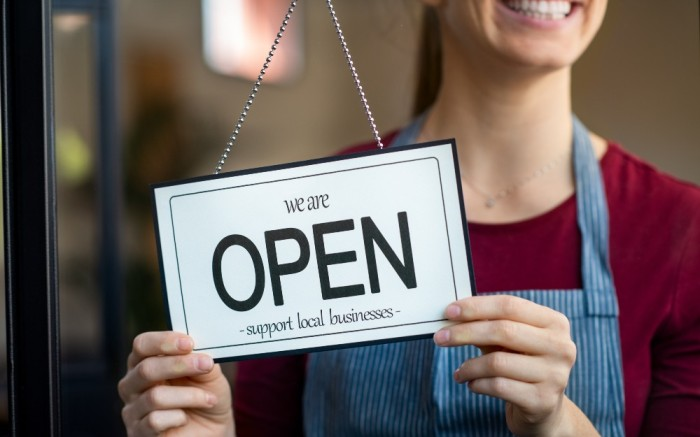 Woman holding store sign saying open support local businesses