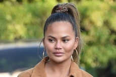 Chrissy Teigen's Classic Trench, Gucci Tights & Sleek Boots Are the Perfect Blend of Winter Trends