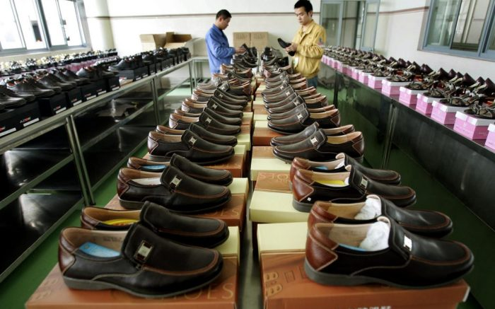 Workers check shoes before shipping out at the production plant of Kangnai Group Co. Thursday, March 30, 2006 in Wenzhou, China. China's government appealed to the European Union last week to reconsider new anti-dumping duties on Chinese shoes, criticizing them as a violation of free trade. (AP Photo/Eugene Hoshiko)