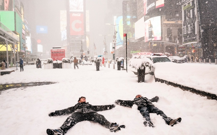 Guy Torres, right, makes snow angels with his relative Diego, left, during a snowstorm in Times Square, Monday, Feb. 1, 2021, in the Manhattan borough of New York. (AP Photo/John Minchillo)