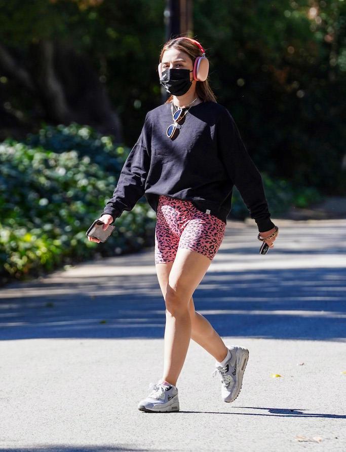 Lucy Hale in Nike sneakers and pink leopard biker shorts in LA