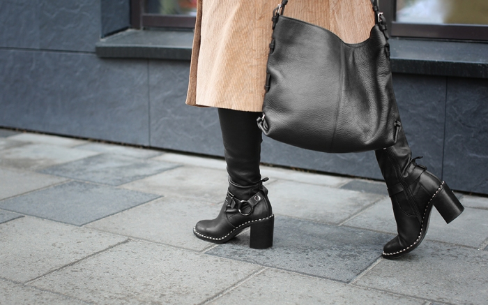Stylish woman in black shoes walking down the street