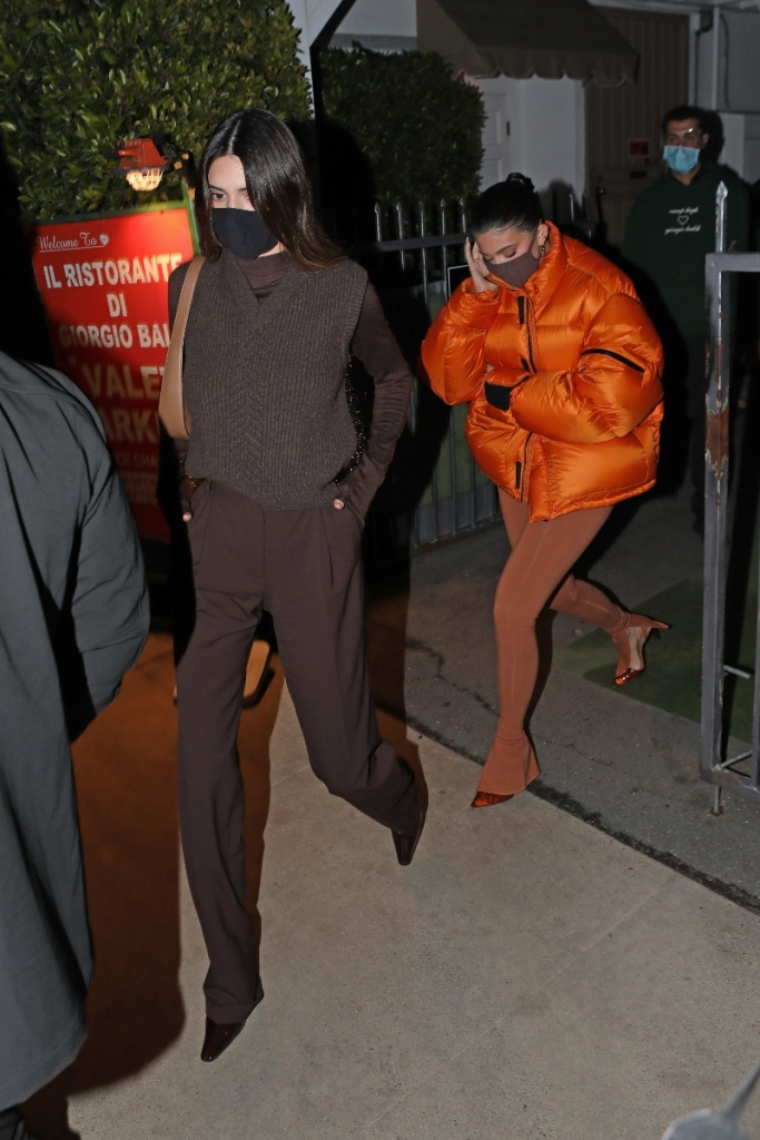 kendall jenner, brown pants, sweater vest, boots, kylie jenner, orange jacket, puffer, tights, boots, dinner, los angeles, skims face mask