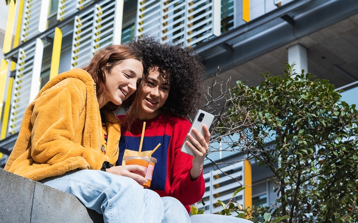 Content multiracial female millennials chatting on social media together on smartphone while sitting with takeaway juice in plastic cups on bench on street