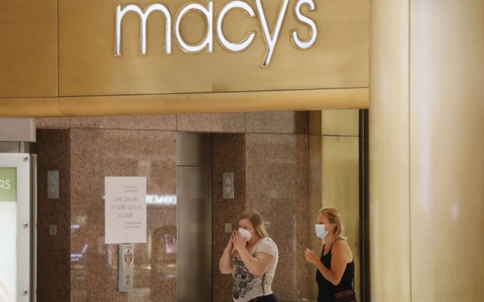 Amid concerns of the spread of COVID-19, shoppers wear masks while walking past a Macy's store at the Galleria Dallas mall in Dallas, Monday, May 4, 2020. (AP Photo/LM Otero)