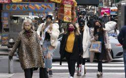 Women carry shopping bags, Thursday, Dec.