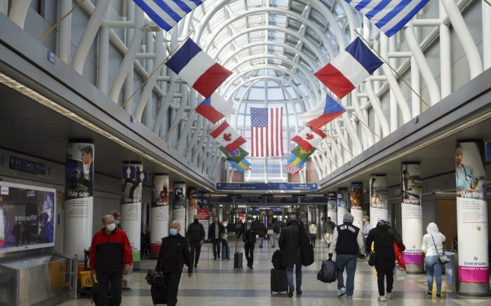 A general view of international flags at the American Airlines Main Hall in Terminal 3 of the O''Hare International Airport, Sunday, Feb. 7, 2021, in Chicago. (Kirby Lee via AP)