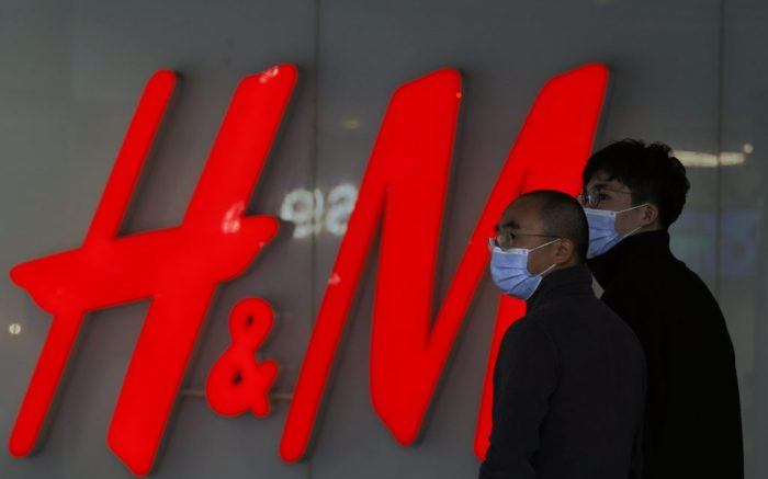Visitors to a shopping mall wearing masks pass by an H&M store in Beijing on Monday, March 29, 2021. China stepped up pressure Monday on foreign shoe and clothing brands to reject reports of abuses in Xinjiang, telling companies that are targeted by Beijing for boycotts to look more closely and pointing to a statement by one that it found no forced labor. (AP Photo/Ng Han Guan)