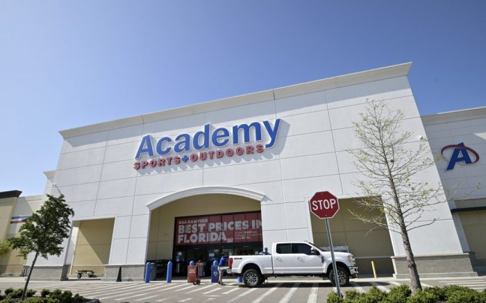 A store employee helps load an item into a truck outside an Academy Sports + Outdoors sporting goods store, Monday, April 20, 2020, in Orlando, Fla. A stay-at-home order is in place due to the new coronavirus pandemic. (Phelan M. Ebenhack via AP)