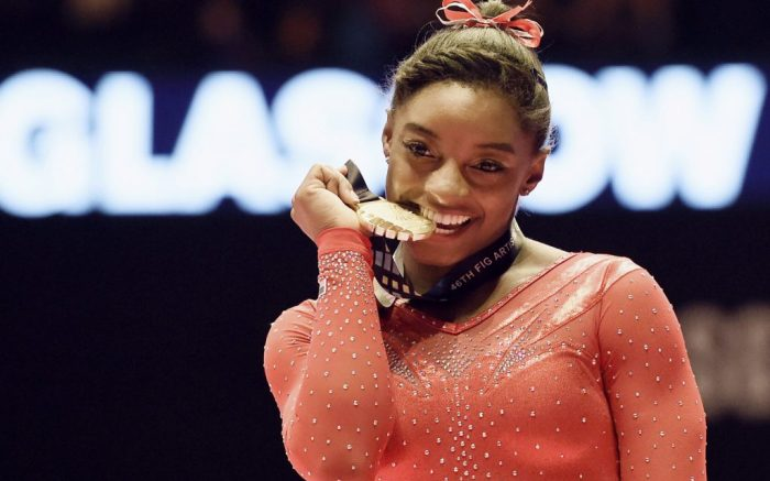Photo taken Oct. 29, 2015, shows Simone Biles of the United States biting her gold medal after winning the women's individual all-around at the world gymnastics championships in Glasgow, Scotland. (Kyodo via AP Images) ==Kyodo