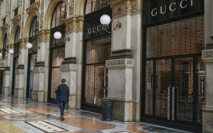 A woman walks past Gucci store inside the Vittorio Emanuele shopping arcade, in Milan, Italy, Friday, Nov. 6, 2020. Lombardy is among the four Italian regions classified as red zones, where a strict lockdown was imposed starting Friday - to be reassessed in two weeks - in an effort to curb the COVID-19 infections growing curve. Starting today, only shops selling food and other essentials are allowed to open. (Gian Mattia D'Alberto/LaPresse via AP)
