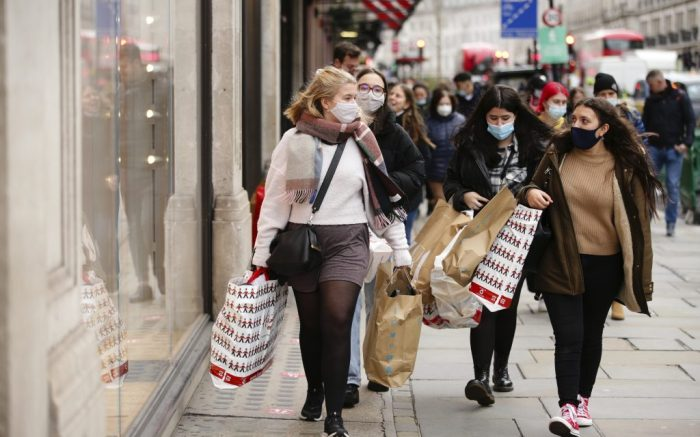 Shoppers wearing face masks carry bags from toy store Hamley's and from fast fashion retailer Primark along Regent Street in London, England, on December 4, 2020. London has returned to so-called Tier 2 or 'high alert' coronavirus restrictions since the end of the four-week, England-wide lockdown on Wednesday, meaning a reopening of non-essential shops and hospitality businesses as the festive season gets underway. Rules under all three of England's tiers have been strengthened from before the November lockdown, however, with pubs and restaurants most severely impacted. In London's West End, Oxford Street and Regent Street were both busy with Christmas shoppers this afternoon, meanwhile, with the retail sector hoping for a strong end to one of its most difficult years. (Photo by David Cliff/NurPhoto via AP)