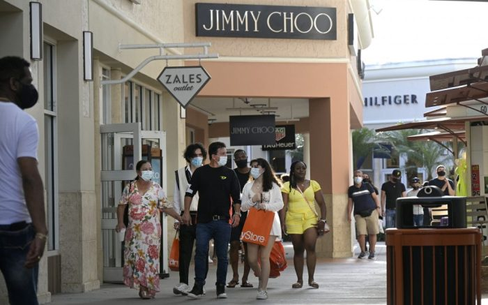 People wear face masks to help curb the spread of COVID-19 outside a Jimmy Choo store at the Orlando Vineland Premium Outlets shopping mall during a new coronavirus pandemic, Saturday, March 27, 2021, in Orlando, Fla. (Phelan M. Ebenhack via AP)
