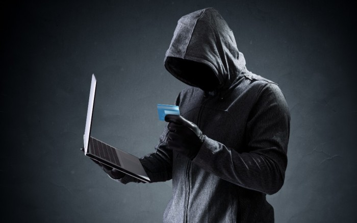 Shadowy figure in a hood holding a credit card as if about to commit online fraud