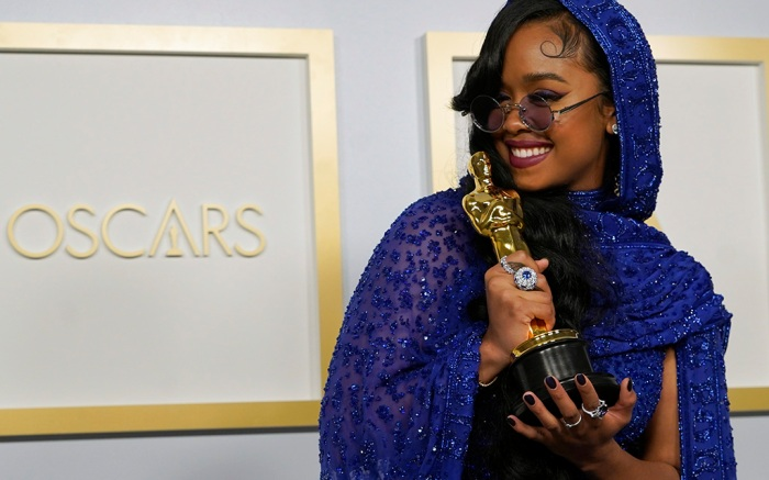 """H.E.R., winner of the award for best original song for """"Fight For You"""" from """"Judas and the Black Messiah,"""" poses in the press room at the Oscars on Sunday, April 25, 2021, at Union Station in Los Angeles. (AP Photo/Chris Pizzello, Pool)"""