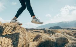 Woman jumping off rock in sneakers