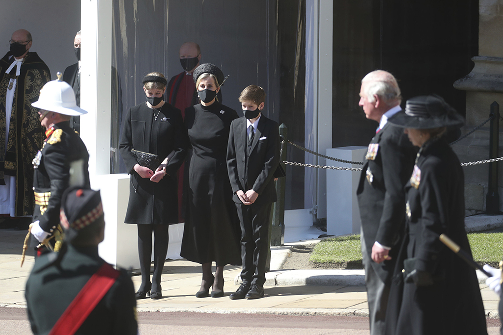 Sophie, the Countess of Wessex, center, Lady Louise Windsor, and James, Viscount Severn watch the procession, as Prince Charles and Princess Anne walk past, from the Galilee Porch of St George's Chapel, Windsor Castle, Windsor, England, Saturday April 17, 2021, during the funeral of Britain's Prince Philip. Prince Philip died April 9 at the age of 99 after 73 years of marriage to Britain's Queen Elizabeth II. (Steve Parsons/Pool via AP)