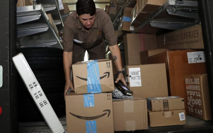 FILE - In this July 17, 2018, file photo UPS employee Liz Perez unloads packages for delivery in Miami. On Monday, July 15, 2019, the first day of Amazon Prime Day's 48-hour sales event, large retailers, those that generated annual revenue of at least a billion dollars, enjoyed a 64% increase in online sales compared with an average Monday, according to Adobe Analytics, which measures 80 of the top 100 retailers on the web in the U.S. (AP Photo/Lynne Sladky, File)