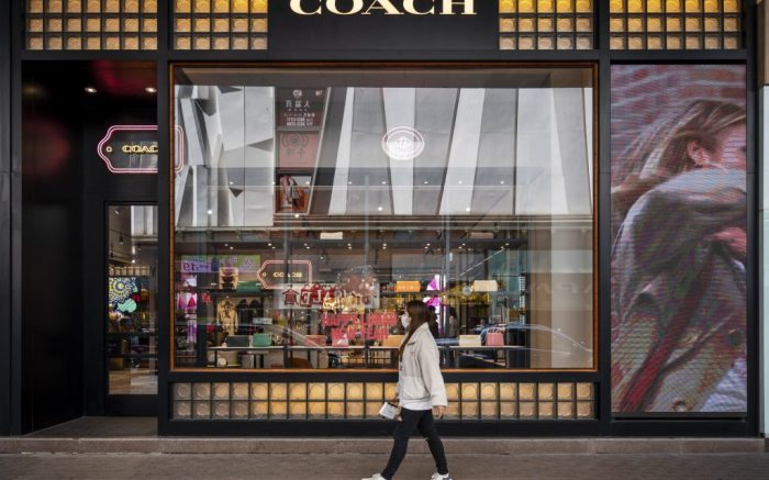 A pedestrian walks past the American multinational fashion and luxury accessories chain brand, Coach store and logo in Hong Kong. (Photo by Budrul Chukrut / SOPA Images/Sipa USA)(Sipa via AP Images)