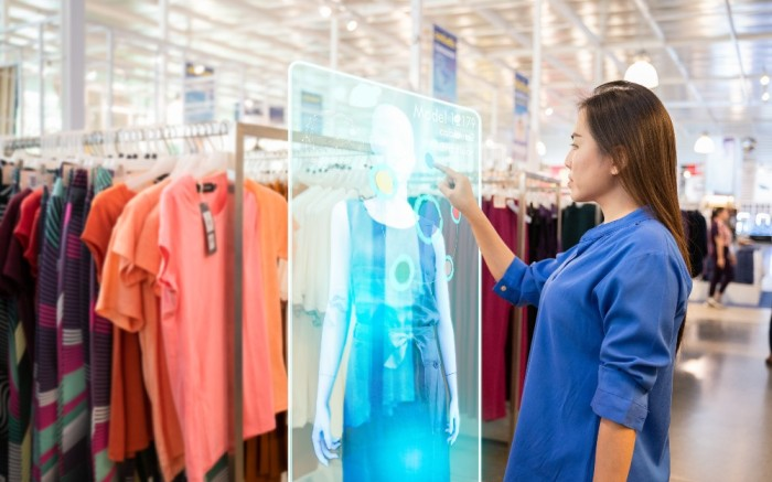 Woman using interactive in-store technology while shopping for apparel
