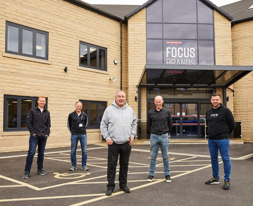 JD Sports executive chairman Peter Cowgill (center) pays a visit to Focus Brands' new headquarters in England.
