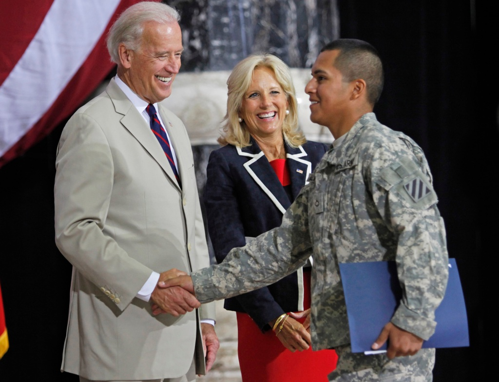 Jill Biden, center, smiles as her husband U.S. Vice President Joe Biden, left, shakes hands with a U.S. Army soldier after his swearing-in at a naturalization ceremony at al-Faw Palace on the western outskirts of Baghdad, Iraq, Sunday, July 4, 2010. Vice President Joe Biden landed Saturday in Baghdad to coax Iraqi leaders into ending their government impasse as vying political factions remain deadlocked over which political bloc should pick its new leaders, including prime minister. (AP Photo/Hadi Mizban)