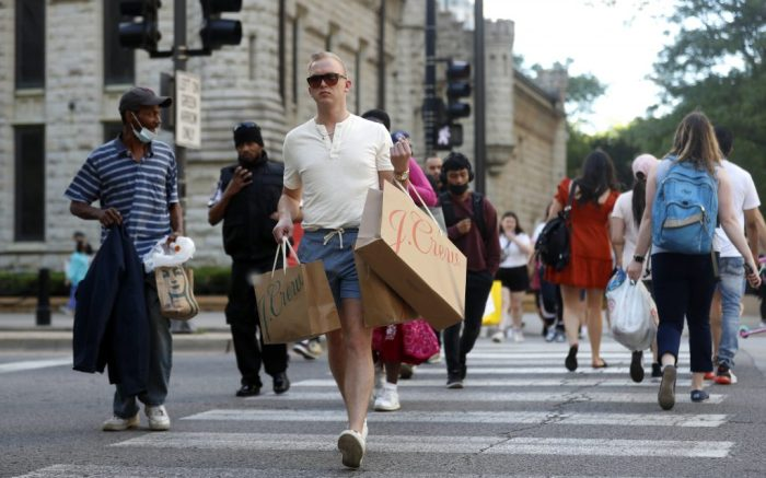 Troy Hemlin visiting Chicago from Springfield Il., crosses the street carrying shopping bags, Wednesday, May 26, 2021, in downtown Chicago. Americans are going back to one of their favorite pastimes: store shopping. With vaccinations rolling out and shoppers freer to go out maskless, retailers are seeing an eager return to their stores after months of watching their customers focus on online buying during the pandemic. (AP Photo/Shafkat Anowar)