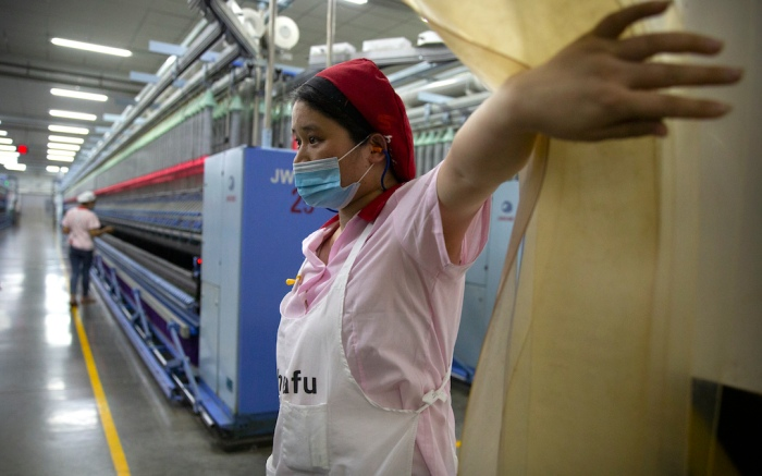 A worker holds open a plastic curtain at a Huafu Fashion plant, as seen during a government organized trip for foreign journalists, in Aksu in western China's Xinjiang Uyghur Autonomous Region, Tuesday, April 20, 2021. A backlash against reports of forced labor and other abuses of the largely Muslim Uyghur ethnic group in Xinjiang is taking a toll on China's cotton industry, but it's unclear if the pressure will compel the government or companies to change their ways. (AP Photo/Mark Schiefelbein)
