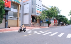 People ride scooters passing closed shops