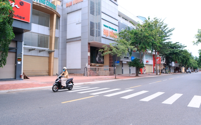 People ride scooters passing closed shops in Vung Tau, Vietnam on Monday, July 19, 2021. Southern Vietnam, with a population of nearly 40 million people, started a two-week lockdown to curb a surge of COVID-19 that is registered at a record number of cases in the country. (AP Photo/ Hau Dinh)