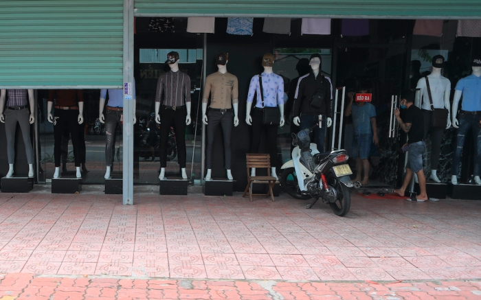 People enter a closed clothing shop in Vung Tau, Vietnam on Monday, July 19, 2021. Southern Vietnam, with a population of nearly 40 million people, started a two-week lockdown to curb a surge of COVID-19 that is registered at a record number of cases in the country. (AP Photo/ Hau Dinh)