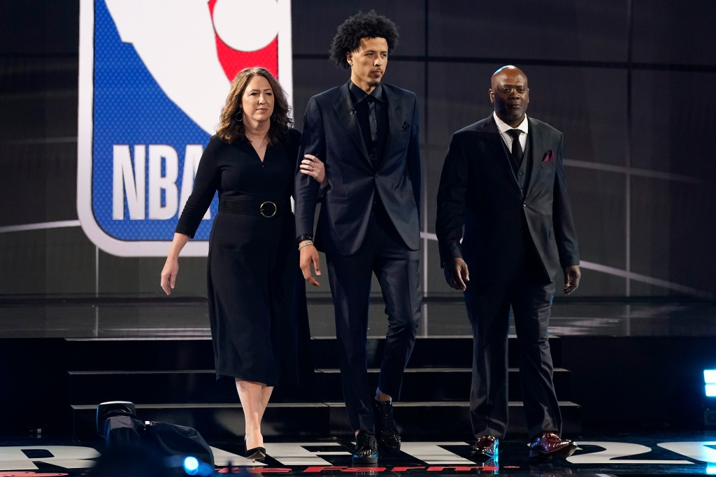 Cade Cunningham, center, walks with his parents, Carrie, left, and Keith Cunningham during the NBA basketball draft, Thursday, July 29, 2021, in New York. Cunningham was selected first overall by the Detroit Pistons. (AP Photo/Corey Sipkin)